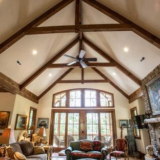 Modelo de sala de estar abierta, de estilo americano, grande, con paredes beige, suelo de madera en tonos medios, chimenea tradicional, marco de chimenea de piedra y televisor colgado en la pared