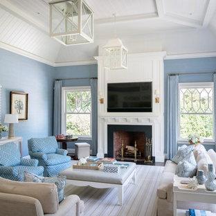 ニューヨークの大きいビーチスタイルのおしゃれなオープンリビング (青い壁、濃色無垢フローリング、標準型暖炉、石材の暖炉まわり、壁掛け型テレビ、茶色い床) の写真