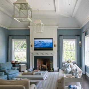 ニューヨークの大きいビーチスタイルのおしゃれなファミリールーム (青い壁、濃色無垢フローリング、標準型暖炉、石材の暖炉まわり、壁掛け型テレビ、茶色い床) の写真