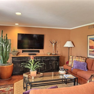 フェニックスの中サイズのサンタフェスタイルのおしゃれなオープンリビング (オレンジの壁、標準型暖炉、石材の暖炉まわり、壁掛け型テレビ) の写真