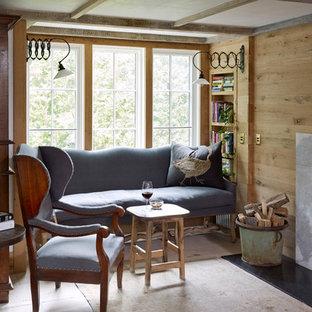 Imagen de sala de estar cerrada, tradicional, pequeña, con paredes beige, suelo de piedra caliza, chimenea tradicional, marco de chimenea de piedra y suelo beige