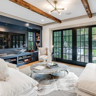 Diseño de sala de estar de estilo de casa de campo con paredes blancas, suelo de madera en tonos medios, televisor colgado en la pared y suelo marrón