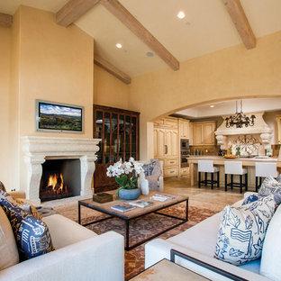 Modelo de sala de estar abierta, campestre, con paredes rosas, suelo de piedra caliza, chimenea tradicional, marco de chimenea de hormigón y pared multimedia