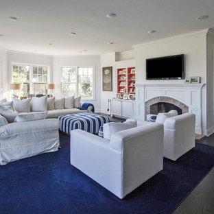 ニューヨークの中くらいのビーチスタイルのおしゃれな独立型ファミリールーム (白い壁、濃色無垢フローリング、標準型暖炉、木材の暖炉まわり、壁掛け型テレビ) の写真