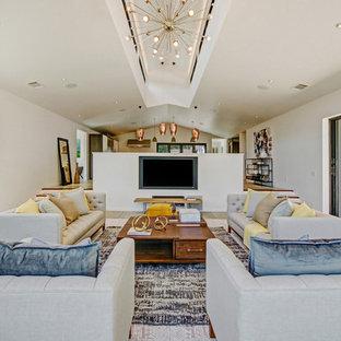 Imagen de sala de estar abierta, campestre, grande, con paredes blancas, suelo de cemento, suelo gris y televisor colgado en la pared
