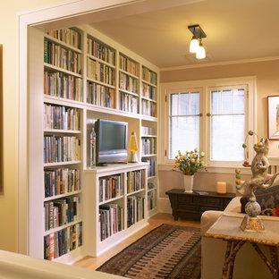 Cette image montre une salle de séjour avec une bibliothèque ou un coin lecture craftsman fermée avec un mur jaune, un sol en bois clair, aucune cheminée et un téléviseur indépendant.