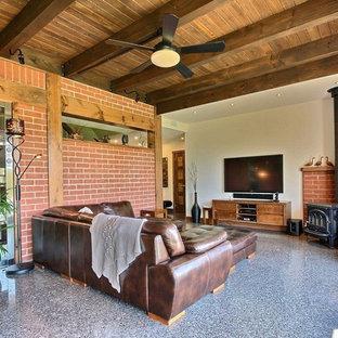 モントリオールの中サイズのコンテンポラリースタイルのおしゃれな独立型ファミリールーム (白い壁、コンクリートの床、薪ストーブ、レンガの暖炉まわり、壁掛け型テレビ、グレーの床) の写真