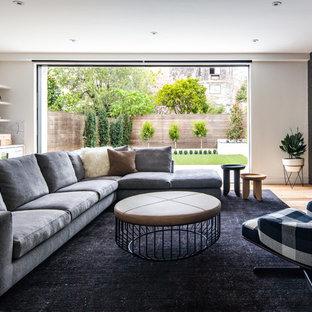 Ejemplo de sala de estar con barra de bar contemporánea con paredes negras, suelo de madera en tonos medios, televisor colgado en la pared y suelo marrón