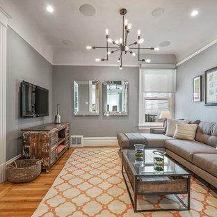 Exempel på ett klassiskt avskilt allrum, med grå väggar, mellanmörkt trägolv, en väggmonterad TV och brunt golv
