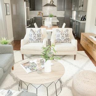 Modelo de sala de estar abierta, moderna, pequeña, con paredes beige, suelo de madera oscura, televisor independiente y suelo marrón