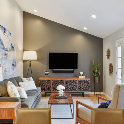 Mid-sized transitional light wood floor family room photo in San Francisco with gray walls, no fireplace and a wall-mounted tv