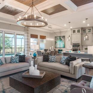 Offenes Maritimes Wohnzimmer mit grauer Wandfarbe, braunem Holzboden und Kassettendecke in Tampa