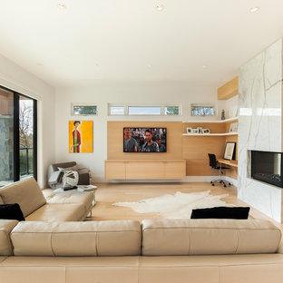 Diseño de sala de estar abierta, escandinava, con paredes blancas, suelo de madera clara, chimenea de doble cara y televisor colgado en la pared