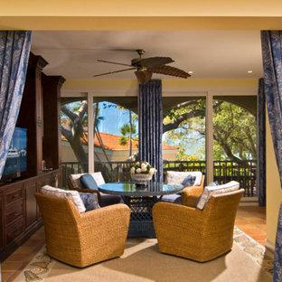 マイアミの中サイズのトロピカルスタイルのおしゃれなファミリールーム (黄色い壁、テラコッタタイルの床、据え置き型テレビ、暖炉なし、茶色い床) の写真