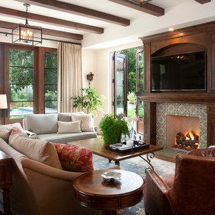 Imagen de sala de estar mediterránea con paredes blancas, pared multimedia, chimenea tradicional y marco de chimenea de baldosas y/o azulejos