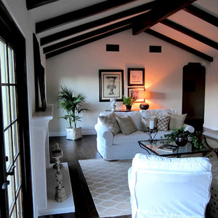 Example of a mid-sized tuscan open concept dark wood floor and brown floor family room design in Santa Barbara with white walls, a standard fireplace and a concrete fireplace