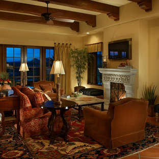 Inspiration for a mid-sized mediterranean open concept terra-cotta floor family room remodel in Phoenix with yellow walls, a standard fireplace, a stone fireplace and a wall-mounted tv