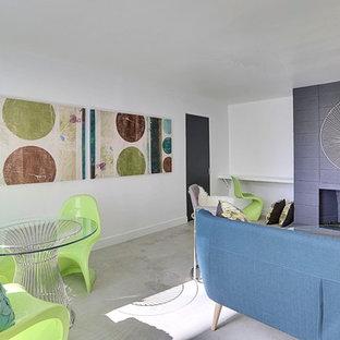 Cette photo montre une grand salle de séjour rétro ouverte avec un mur blanc, béton au sol, une cheminée standard et un manteau de cheminée en béton.