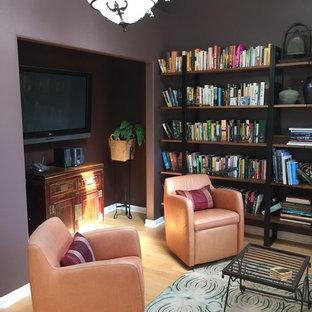 Immagine di un piccolo soggiorno contemporaneo aperto con pareti viola, TV a parete, libreria e parquet chiaro