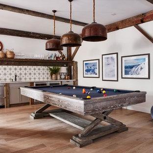 Modelo de sala de juegos en casa abierta, de estilo de casa de campo, con paredes blancas y suelo de madera clara