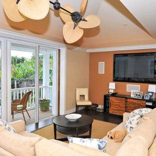 Cette photo montre une salle de séjour tendance de taille moyenne et fermée avec un mur orange, un sol en bois foncé, aucune cheminée, un téléviseur fixé au mur et un sol marron.