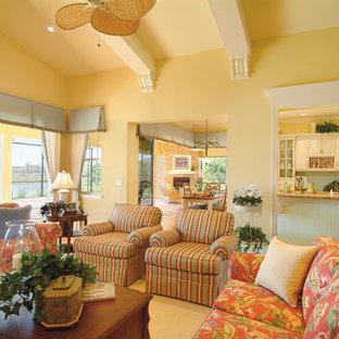 Diseño de sala de estar abierta, campestre, grande, sin chimenea, con paredes amarillas, suelo de madera en tonos medios y televisor independiente