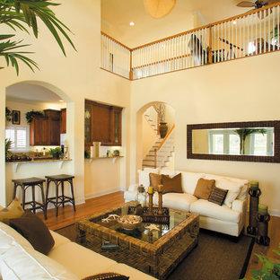 マイアミの大きいビーチスタイルのおしゃれなファミリールーム (黄色い壁、無垢フローリング、標準型暖炉、石材の暖炉まわり、壁掛け型テレビ) の写真