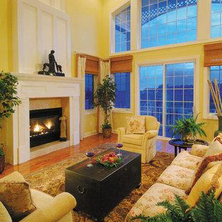マイアミの大きいビーチスタイルのおしゃれなオープンリビング (黄色い壁、無垢フローリング、標準型暖炉、石材の暖炉まわり、テレビなし) の写真