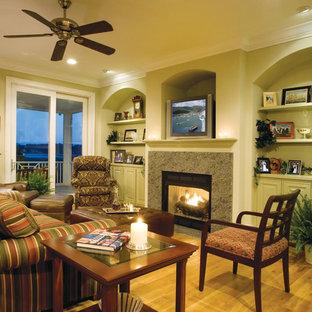 マイアミの大きいビーチスタイルのおしゃれなオープンリビング (ホームバー、緑の壁、無垢フローリング、標準型暖炉、石材の暖炉まわり、埋込式メディアウォール) の写真
