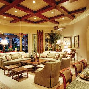 Idee per un grande soggiorno mediterraneo aperto con angolo bar, pareti beige, pavimento in legno massello medio, nessun camino e parete attrezzata