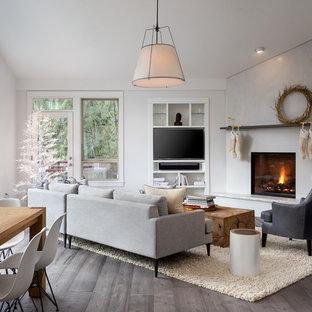 Cette photo montre une grande salle de séjour scandinave ouverte avec un mur blanc, une cheminée d'angle, un manteau de cheminée en béton, un téléviseur encastré, un sol en bois foncé et un sol gris.