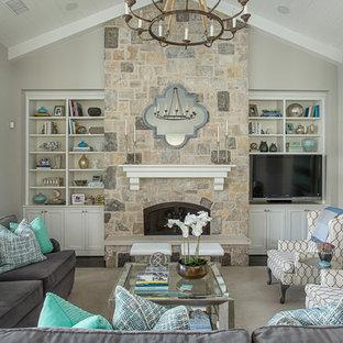 Cette image montre une salle de séjour marine avec un mur gris, un sol en bois foncé, une cheminée standard, un manteau de cheminée en pierre et un téléviseur encastré.