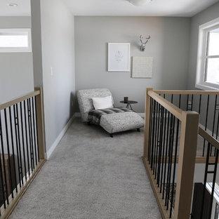 Ejemplo de sala de estar con biblioteca abierta, clásica renovada, pequeña, sin chimenea y televisor, con paredes grises y moqueta