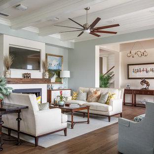 ジャクソンビルのビーチスタイルのおしゃれなファミリールーム (青い壁、無垢フローリング、標準型暖炉、金属の暖炉まわり、壁掛け型テレビ、茶色い床) の写真