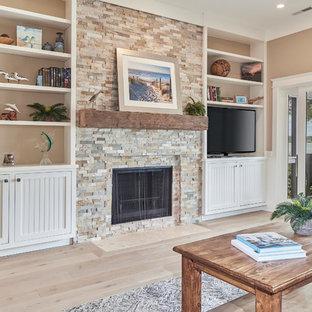アトランタの大きいビーチスタイルのおしゃれなファミリールーム (ライブラリー、ベージュの壁、淡色無垢フローリング、標準型暖炉、石材の暖炉まわり、据え置き型テレビ、ベージュの床) の写真