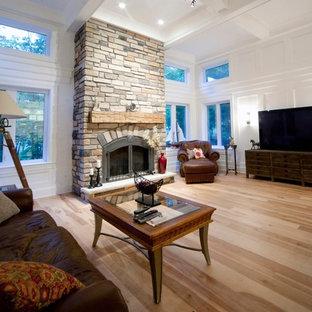 Imagen de sala de estar abierta, tradicional, grande, con paredes blancas, suelo de madera en tonos medios, estufa de leña, marco de chimenea de piedra y suelo multicolor