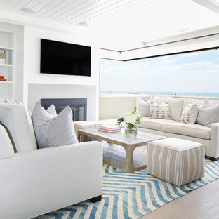 オレンジカウンティの大きいビーチスタイルのおしゃれなファミリールーム (白い壁、淡色無垢フローリング、標準型暖炉、石材の暖炉まわり、壁掛け型テレビ、茶色い床) の写真