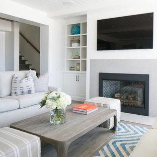 オレンジカウンティのビーチスタイルのおしゃれなファミリールーム (白い壁、標準型暖炉、石材の暖炉まわり) の写真