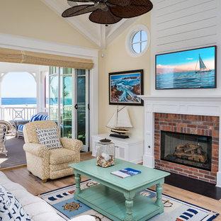 Foto de sala de estar marinera, grande, con paredes amarillas, suelo de madera clara, chimenea lineal, marco de chimenea de ladrillo y televisor colgado en la pared