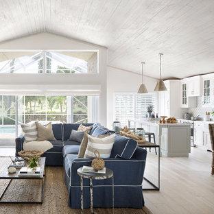 Réalisation d'une salle de séjour marine de taille moyenne et ouverte avec un sol en bois clair, aucune cheminée et un mur blanc.