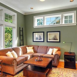 Réalisation d'une salle de séjour craftsman avec un mur vert, un sol en bois brun et un téléviseur indépendant.