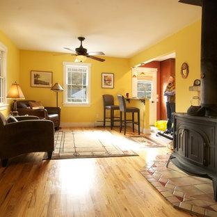 Idee per un soggiorno american style di medie dimensioni e aperto con pareti gialle, pavimento in legno massello medio e stufa a legna