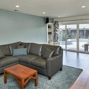 サンフランシスコの中サイズのコンテンポラリースタイルのおしゃれなオープンリビング (青い壁、ラミネートの床、据え置き型テレビ、茶色い床) の写真