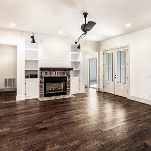 Idées déco pour une salle de séjour mansardée ou avec mezzanine campagne de taille moyenne avec un mur blanc, un sol en bois foncé, un poêle à bois, un manteau de cheminée en brique, un sol marron et aucun téléviseur.