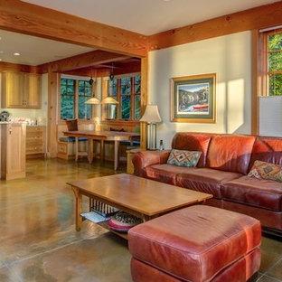 Aménagement d'une grande salle de séjour craftsman ouverte avec un mur beige et béton au sol.