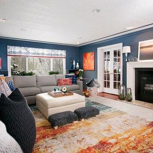 ニューヨークの中くらいのモダンスタイルのおしゃれな独立型ファミリールーム (青い壁、カーペット敷き、標準型暖炉、石材の暖炉まわり、壁掛け型テレビ) の写真