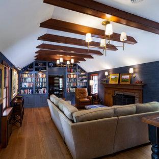 Diseño de sala de estar con biblioteca cerrada, de estilo de casa de campo, con paredes azules, suelo de madera clara, chimenea tradicional y marco de chimenea de ladrillo