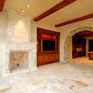 Family room - mid-sized rustic enclosed limestone floor family room idea in Orange County with beige walls, a standard fireplace, a stone fireplace and a media wall