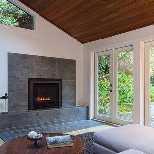 Cette image montre une grande salle de séjour minimaliste ouverte avec un mur blanc, un sol en carrelage de porcelaine, une cheminée standard et un manteau de cheminée en béton.