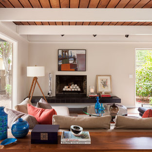 Large 1950s family room photo in San Francisco with white walls, a standard fireplace and no tv